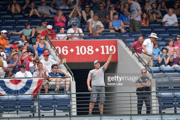 A fan catches a foul ball hit by Ryan Howard of the Philadelphia Phillies during the ninth inning at Turner Field on June 18 2014 in Atlanta Georgia