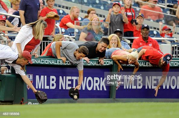 A fan catches a foul ball in a hat during the ninth inning of the game between the Washington Nationals and the Arizona Diamondbacks at Nationals...