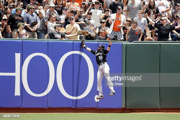 A fan catches a home run ball hit by Hunter Pence of the San Francisco Giants as Charlie Blackmon of the Colorado Rockies leaps into the air to try...