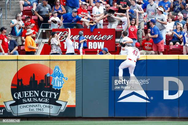 A fan catches a home run ball hit by Jon Jay of the Chicago Cubs as Scott Schebler of the Cincinnati Reds looks up in the third inning of a game at...