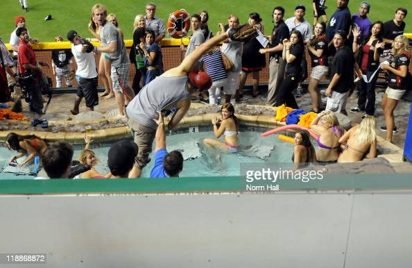 A fan catches a home run ball in the pool during the 2011 State Farm Home Run Derby at Chase Field on July 11 2011 in Phoenix Arizona
