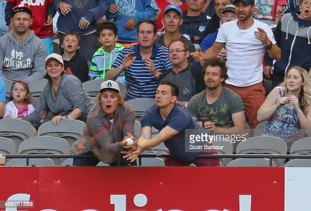 A fan catches a six in the crowd during the Big Bash League match between the Melbourne Renegades and Brisbane Heat at Etihad Stadium on December 30...