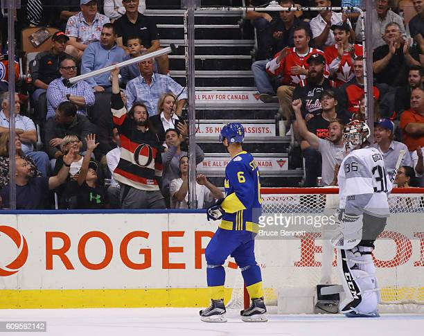 A fan catches the goal light and shows it off to fans after it fell from the glass during the second period between the Team Sweden and the Team...