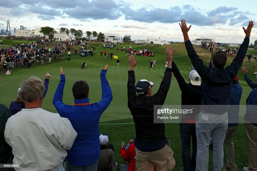 Fan cheer after Charlie Hoffman of the U.S. Team celebrates after chipping in on the 17th hole during Saturday four-ball matches of the Presidents Cup at Liberty National Golf Club on September 30, 2017 in Jersey City, New Jersey.