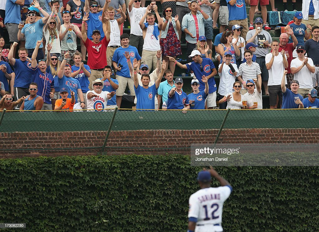 Fan cheer <a gi-track='captionPersonalityLinkClicked' href=/galleries/search?phrase=Alfonso+Soriano&family=editorial&specificpeople=202251 ng-click='$event.stopPropagation()'>Alfonso Soriano</a> #12 of the Chicago Cubs after hitting his second two-run home run of the game in the 5th inning against the Pittsburgh Pirates at Wrigley Field on July 6, 2013 in Chicago, Illinois.