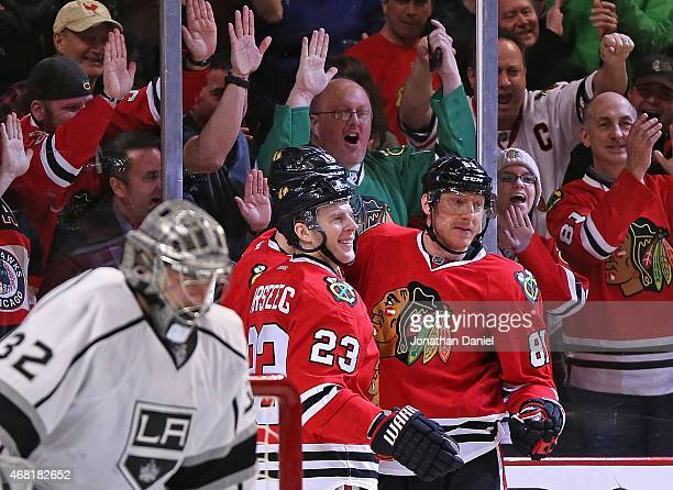 Fan cheer as Kris Versteeg Jonathan Toews and Marian Hossa of the Chicago Blackhawks celebrate Hossa's third period goal against Jonathan Quick of...