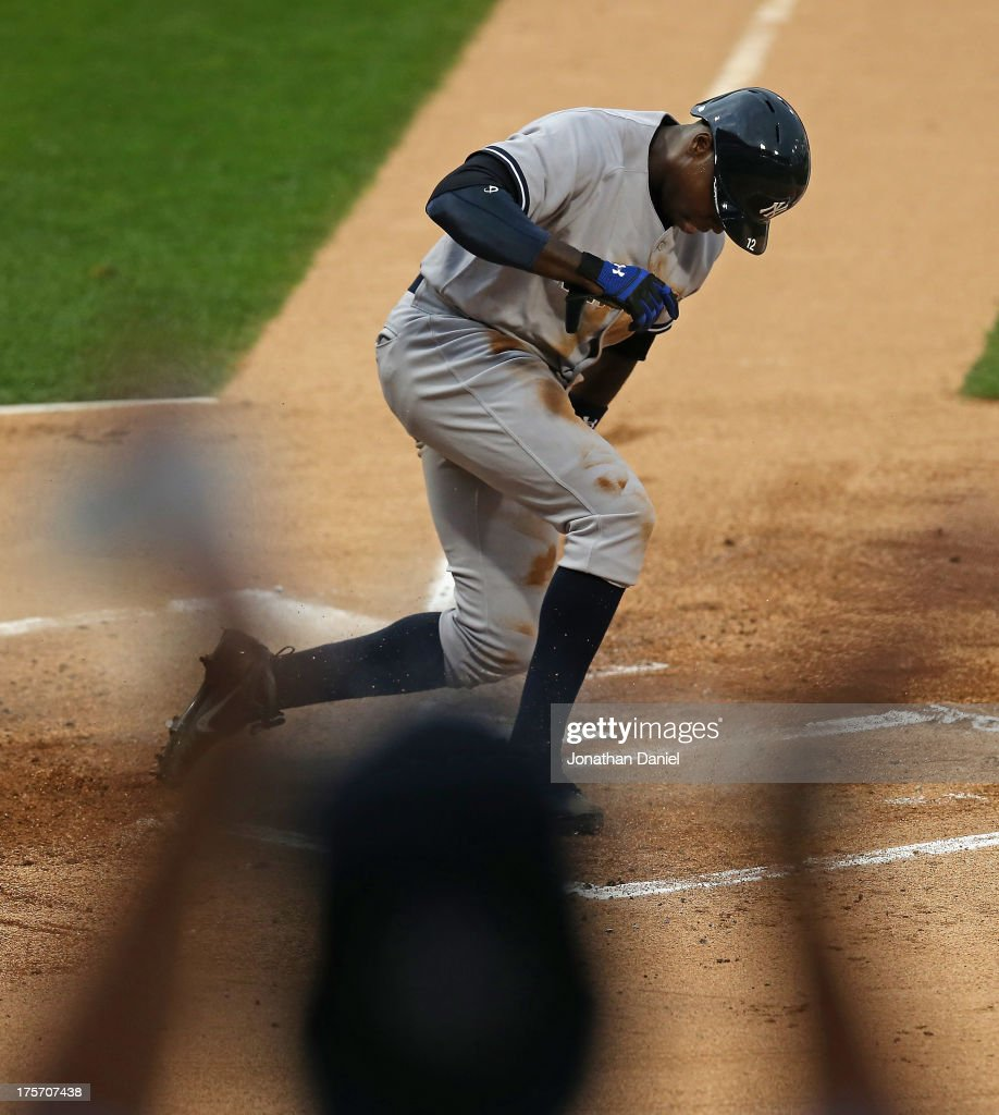 A fan cheers as <a gi-track='captionPersonalityLinkClicked' href=/galleries/search?phrase=Alfonso+Soriano&family=editorial&specificpeople=202251 ng-click='$event.stopPropagation()'>Alfonso Soriano</a> #12 of the New York Yankees scores a run on a wild pitch in the 1st inning against the Chicago White Sox at U.S. Cellular Field on August 6, 2013 in Chicago, Illinois.