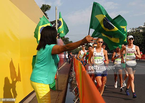 A fan cheers as Matej Toth of Slovakia and Evan Dunfee of Canada compete in the Men's 50km Race Walk on Day 14 of the Rio 2016 Olympic Games at...