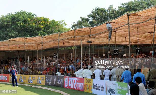A fan climbs on to the roof of the stand after India's Virender Sehwag hit a six during The First One Day International at Madhavrao Scindia Cricket...