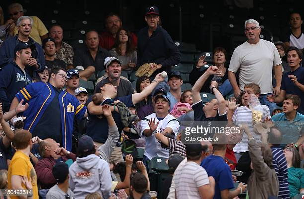 A fan cradling a baby reaches for a foul ball by Michael Saunders of the Seattle Mariners during the game against the Minnesota Twins at Safeco Field...