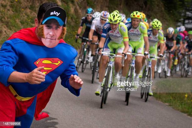 A fan disguised as a Superman character poses as the pack rides in the 1435 km and seventeenth stage of the 2012 Tour de France cycling race starting...