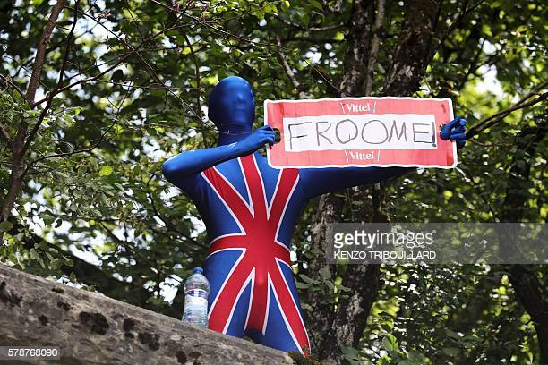 A fan disguised with colours of the Great Britain's Union Jack flag and holding a placard reading [Great Britain's Christopher] Froome cheers along...