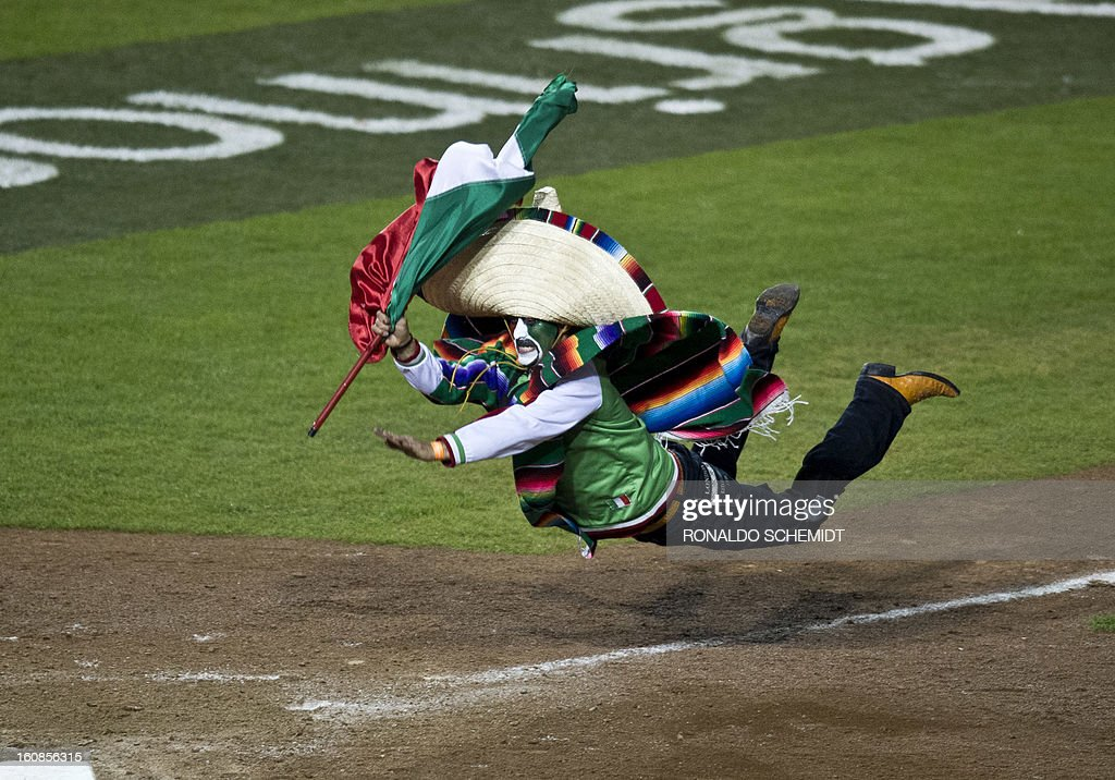 A fan dives into home plate after running out onto the field of Sonora Stadium during a match between Yaquis de Obregon of Mexico and Criollos de Caguas of Puerto Rico at the 2013 Caribbean baseball series on February 6, 2013, in Hermosillo in the northern Mexican state of Sonora. The Mexican team won 10-0. AFP PHOTO/Ronaldo Schemidt