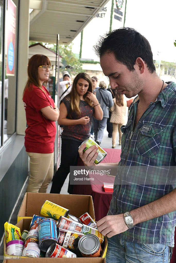 A fan donates canned food items at Cost Plus World Market's Share the Joy event with celebrity chef Curtis Stone at Cost Plus World Market on December 8, 2012 in Los Angeles, United States.