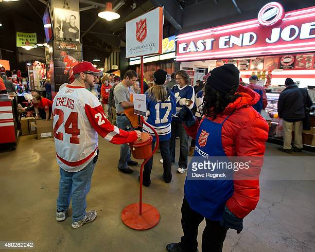 A fan donates to the Salvation Army red kettle before an NHL game between the Detroit Red Wings and the Toronto Maple Leafs on December 10 2014 at...