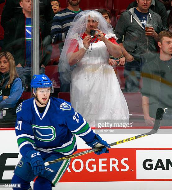 A fan dressed as a bride lookson as Ben Hutton of the Vancouver Canucks skates up ice during their NHL game against the St Louis Blues at Rogers...