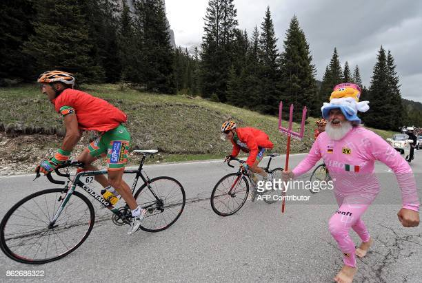 A fan dressed as a devil runs with Italy's Emanuele Sella and Fortunato Baliani during the 15th stage of the 91st Giro d'Italia from Arabba to Passo...