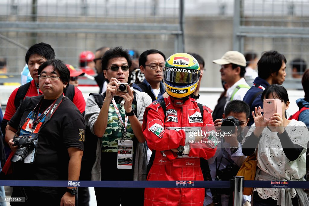 A fan dressed as Ayrton Senna looks on outside the Red Bull Racing garage during previews ahead of the Formula One Grand Prix of Japan at Suzuka Circuit on October 5, 2017 in Suzuka.