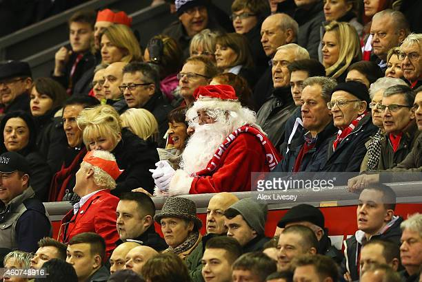 A fan dressed as Father Christmas watches the Barclays Premier League match between Liverpool and Arsenal at Anfield on December 21 2014 in Liverpool...