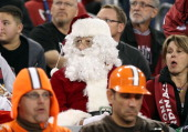 A fan dressed as Santa Claus attends the NFL game between the Cleveland Browns and the Arizona Cardinals at the University of Phoenix Stadium on...