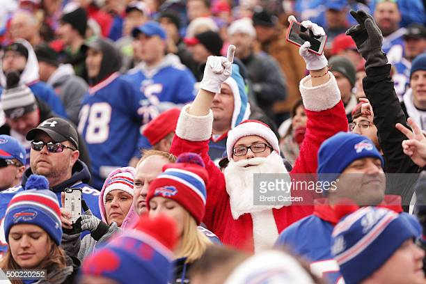 A fan dressed as Santa Claus cheers during the first half against the Houston Texans at Ralph Wilson Stadium on December 6 2015 in Orchard Park New...