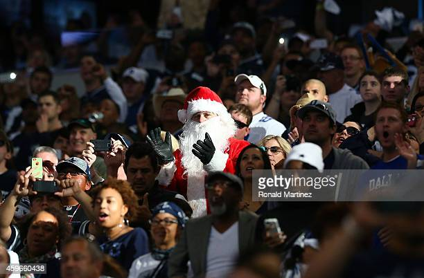 A fan dressed as Santa Claus claps before the start of the Thanksgiving Day game between the Philadelphia Eagles and the Dallas Cowboys at ATT...