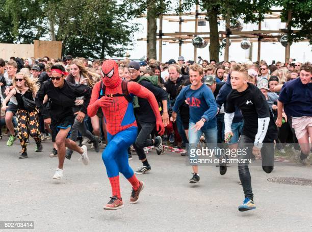 A fan dressed as spider man rushes besides other rock fans through the gate during the opening of the Roskilde Festival on June 28 2017 in Roskilde...