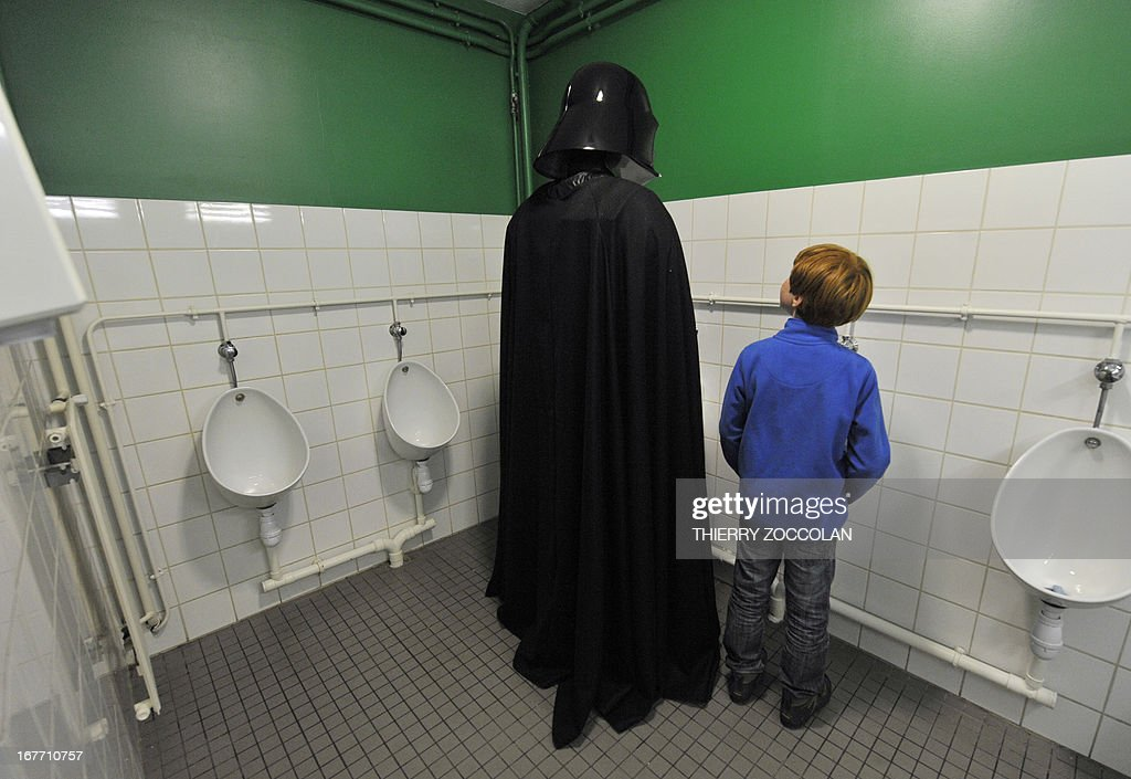 A fan dressed as the character of Darth Vader (Dark Vador in French) is pictured in public toilets during a Star Wars convention on April 27, 2013 in Cusset.