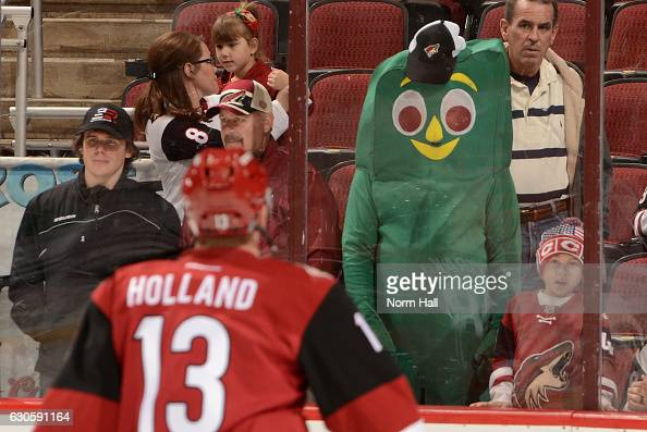 A fan dressed in a Gumby costume watches pregame as Peter Holland of the Arizona Coyotes skates by prior to a game against the Dallas Stars at Gila...