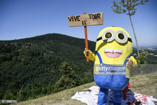 A fan dressed up as a Minion character hold a placard reading 'Long live the Tour [de France]' along the road during the 165 km sixteenth stage of...