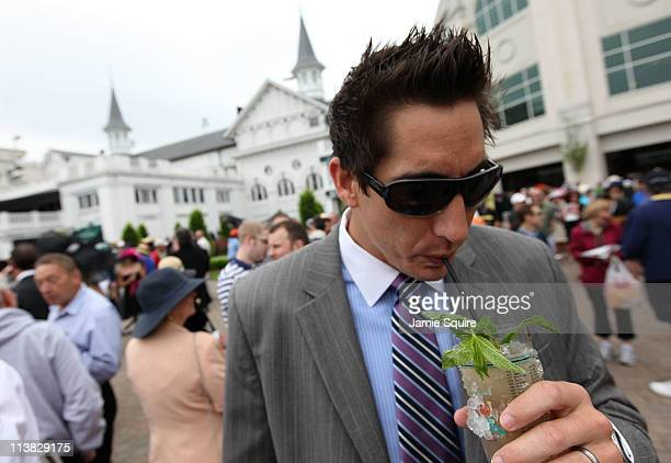 A fan drinks a mint julep in the paddock area during the 137th Kentucky Derby at Churchill Downs on May 7 2011 in Louisville Kentucky