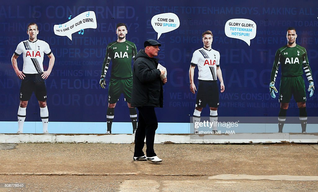A fan, eating chips, walks past pictures of Harry Kane, Hugo Lloris, Christian Eriksen and Michael Vorm of Tottenham Hotspur and underneath a sign saying Come on you Spurs prior to the Barclays Premier League match between Tottenham Hotspur and Watford at White Hart Lane on February 6, 2016 in London, England.