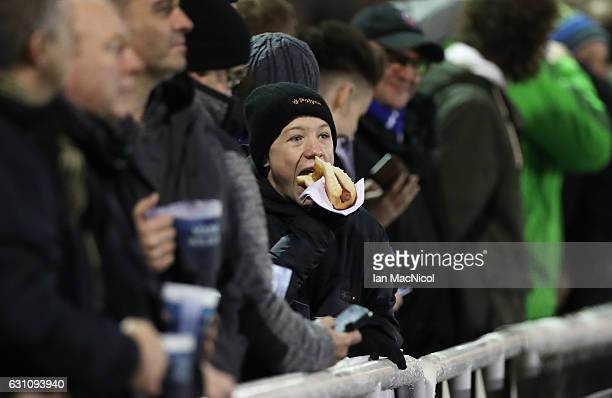 A fan eats a hotdog during the Aviva Premiership match between Newcastle Falcons and Bath Rugby at Kingston Park on January 6 2017 in Newcastle upon...