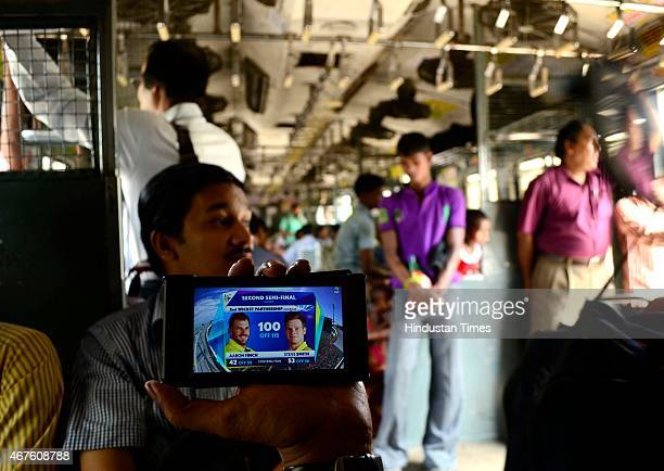 A fan enjoying India vs Australia Cricket World cup semifinal match on smartphone while on his way to work on a train on March 26 2015 in Kolkata...