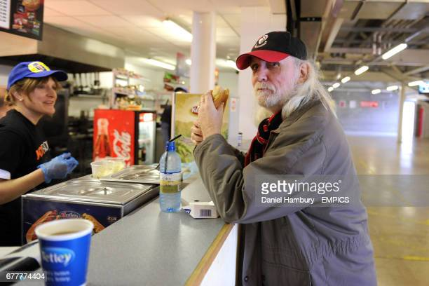 A fan enjoys a hotdog at one of the refreshment bars in the concourses at Dean Court stadium