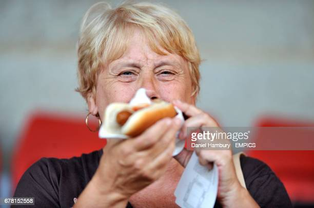 A fan enjoys a hotdog in the stands before the game