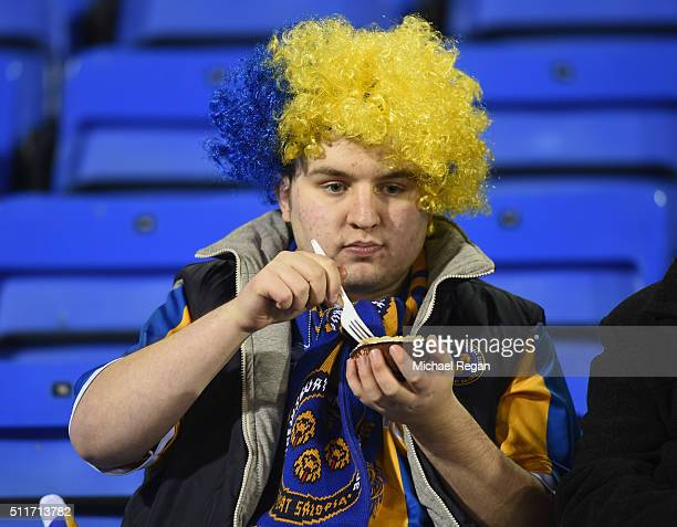 A fan enjoys a prematch pie prior to the Emirates FA Cup fifth round match between Shrewsbury Town and Manchester United at Greenhous Meadow on...
