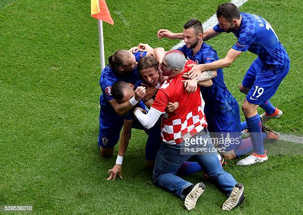 TOPSHOT A fan enters onto the pitch to celebrates with Croatia's midfielder Luka Modric and his teammates after Modric scored the team's first goal...