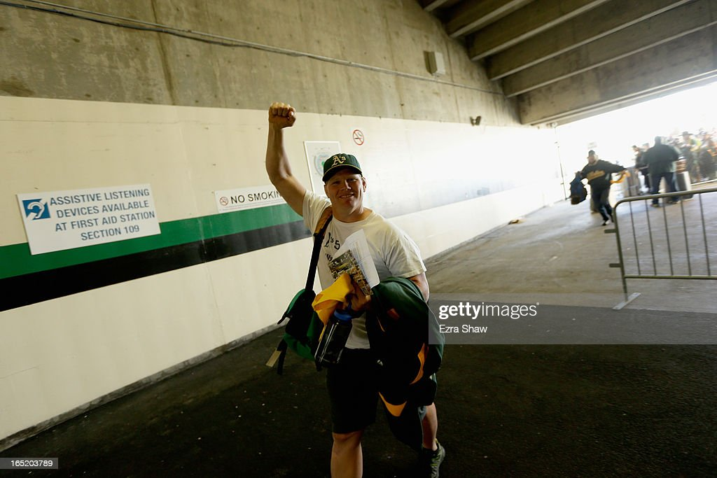 A fan enters the stadium for the Oakland Athletics game against the Seattle Mariners on Opening Day at O.co Coliseum on April 1, 2013 in Oakland, California.