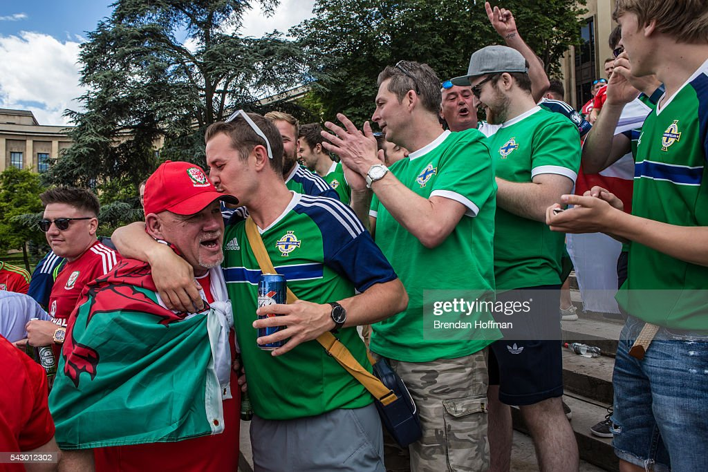 A fan from Northern Ireland kisses a Welsh fan ahead of the football match between Wales and Northern Ireland during UEFA Euro 2016 tournament on June 25, 2016 in Paris, France. Wales edged Northern Ireland in the Round of 16 at Parc des Princes in Paris.