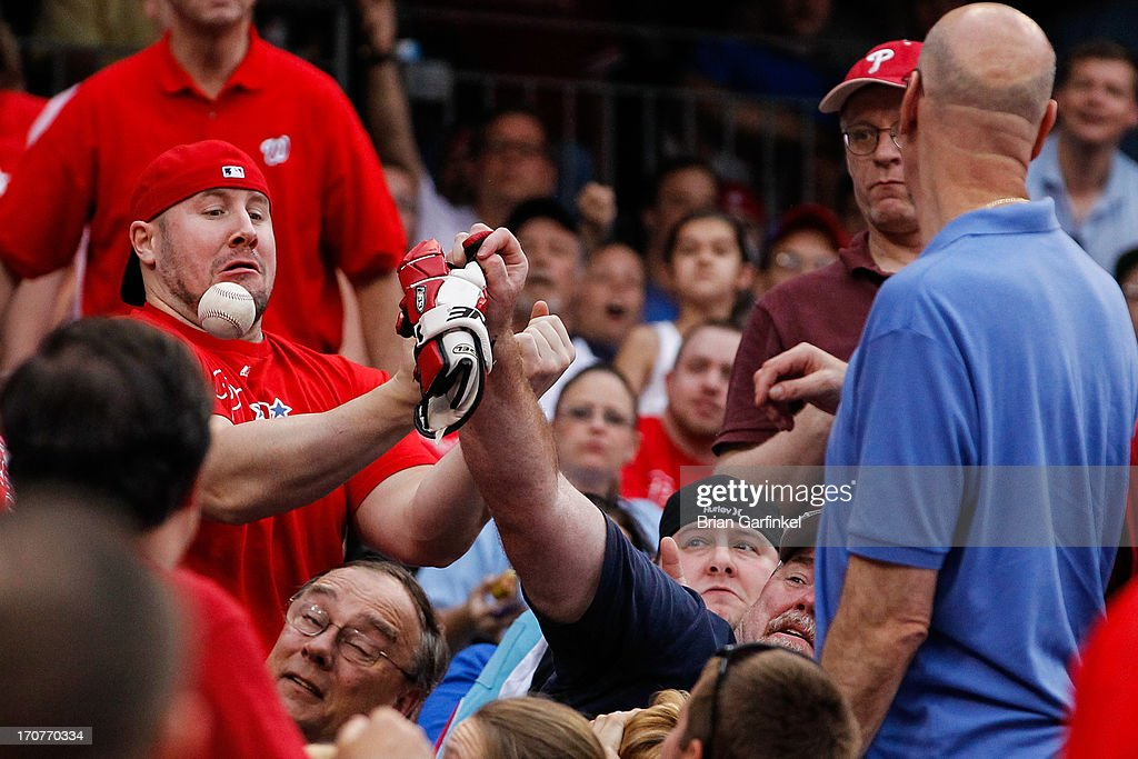 A fan fumbles a foul ball hit by Ryan Howard (not pictured) of the Philadelphia Phillies in the second inning of the game against the Washington Nationals at Citizens Bank Park on June 17, 2013 in Philadelphia, Pennsylvania.