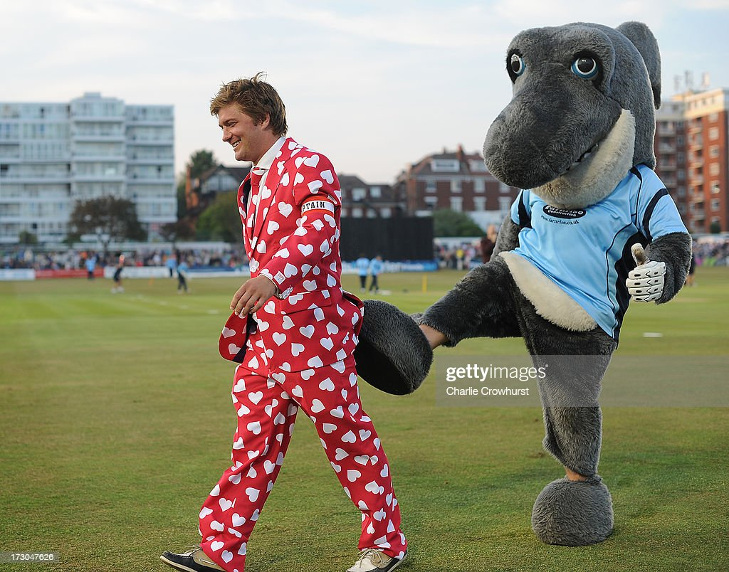 A fan gets a kick from the Sussex mascot during the Friends Life T20 match between Sussex Sharks and Hampshire Royals at The Brighton and Hove Jobs County Ground on July 05, 2013 in Hove, England.