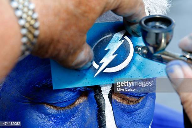 A fan gets a stencil of the Tampa Bay Lightning logo painted on his forehead prior to Game Four of the Eastern Conference Finals against the New York...