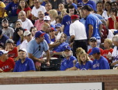 A fan gets hit in the face by a line drive foul ball during the game between the Boston Red Sox and the Texas Rangers at Rangers Ballpark in...