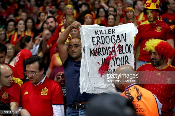 A fan holds a banner aimed at Turkish President Recep Tayyip Erdogan in the stands