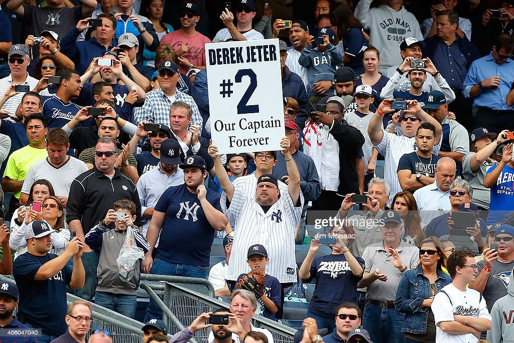 A fan holds a banner in reference to Derek Jeter #2 of the New York Yankees during the eighth inning against the Baltimore Orioles at Yankee Stadium on September 24, 2014 in the Bronx borough of New York City.