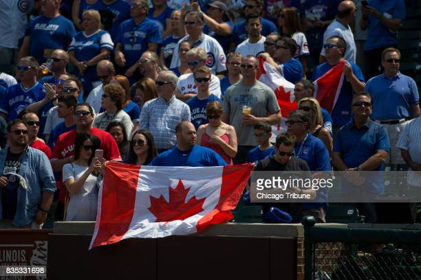 A fan holds a Canadian flag during the Canadian national anthem as the Chicago Cubs play host to the Toronto Blue Jays on Friday Aug 18 at Wrigley...