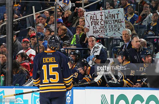A fan holds a Christmas wish sign as Jack Eichel of the Buffalo Sabres skates to the bench during an NHL game against the Anaheim Ducks on December...