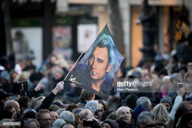 A fan holds a flag of singer Johnny Hallyday during Johnny Hallyday's funerals at Eglise De La Madeleine on December 9 2017 in Paris France France...
