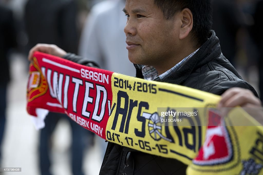 A fan holds a matchday scarf outside Old Trafford stadium before the English Premier League football match between Manchester United and Arsenal at...